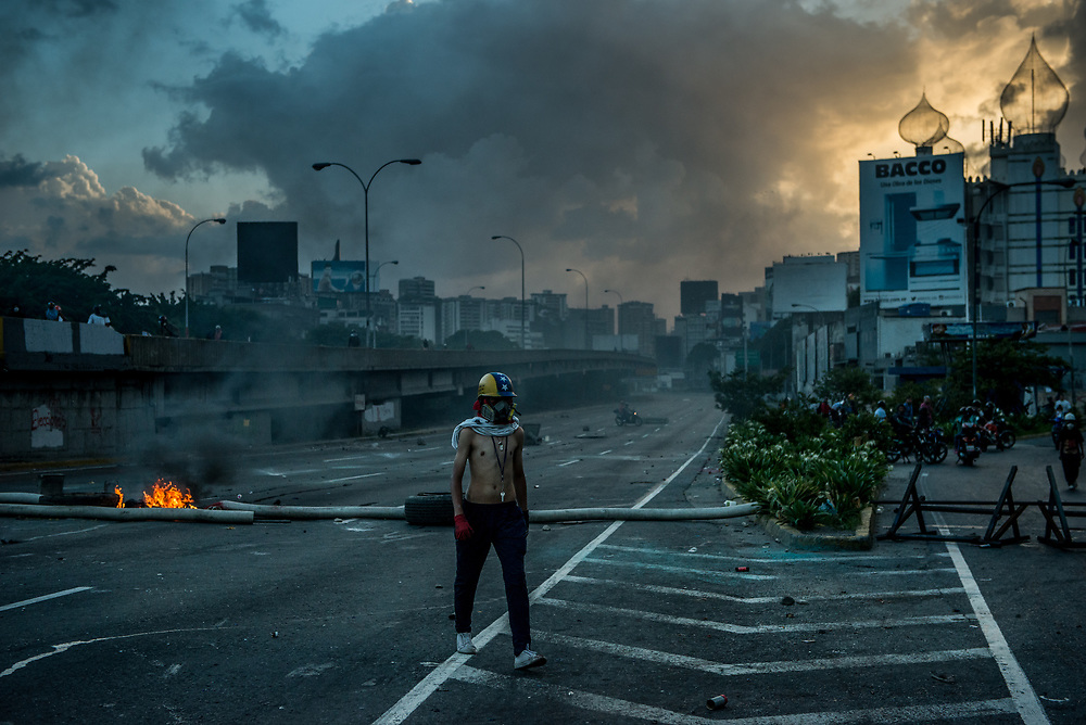 CARACAS, VENEZUELA - MAY 26, 2017:  Anti-government protesters occupy the main highway that runs through Caracas. The streets of Caracas and other cities across Venezuela have been filled with tens of thousands of demonstrators for nearly 100 days of massive protests, held since April 1st. Protesters are enraged at the government for becoming an increasingly repressive, authoritarian regime that has delayed elections, used armed government loyalist to threaten dissidents, called for the Constitution to be re-written to favor them, jailed and tortured protesters and members of the political opposition, and whose corruption and failed economic policy has caused the current economic crisis that has led to widespread food and medicine shortages across the country.  Independent local media report nearly 100 people have been killed during protests and protest-related riots and looting.  The government currently only officially reports 75 deaths.  Over 2,000 people have been injured, and over 3,000 protesters have been detained by authorities.  PHOTO: Meridith Kohut