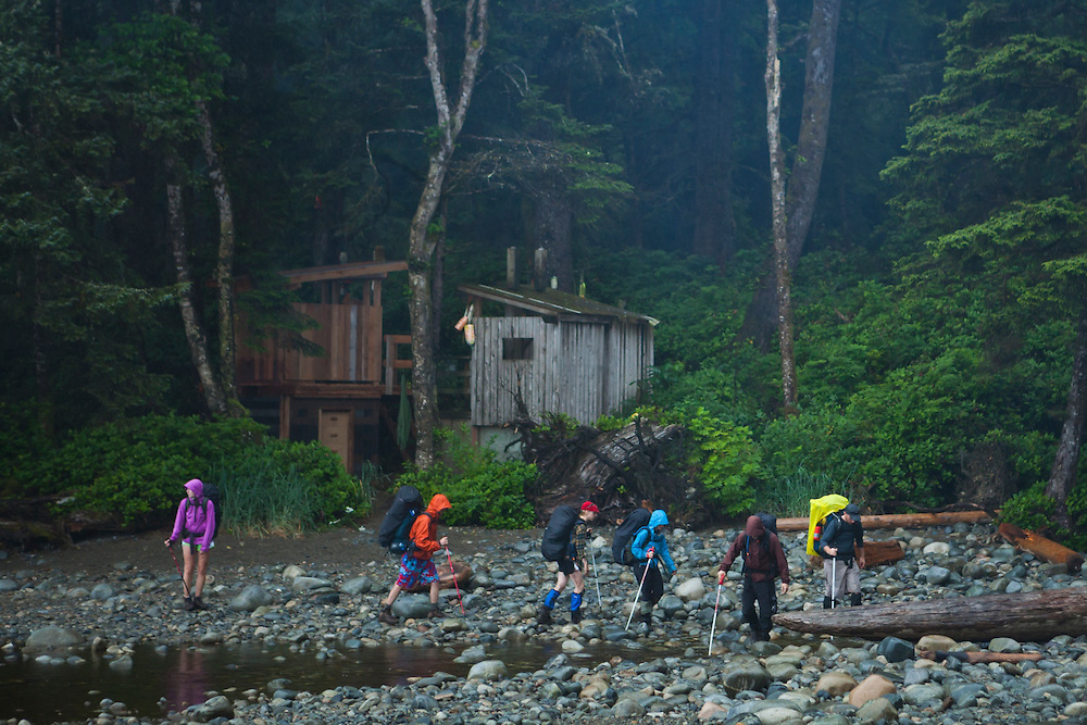 A group of hikers cross Michigan Creek, West Coast Trail, British Columbia, Canada.