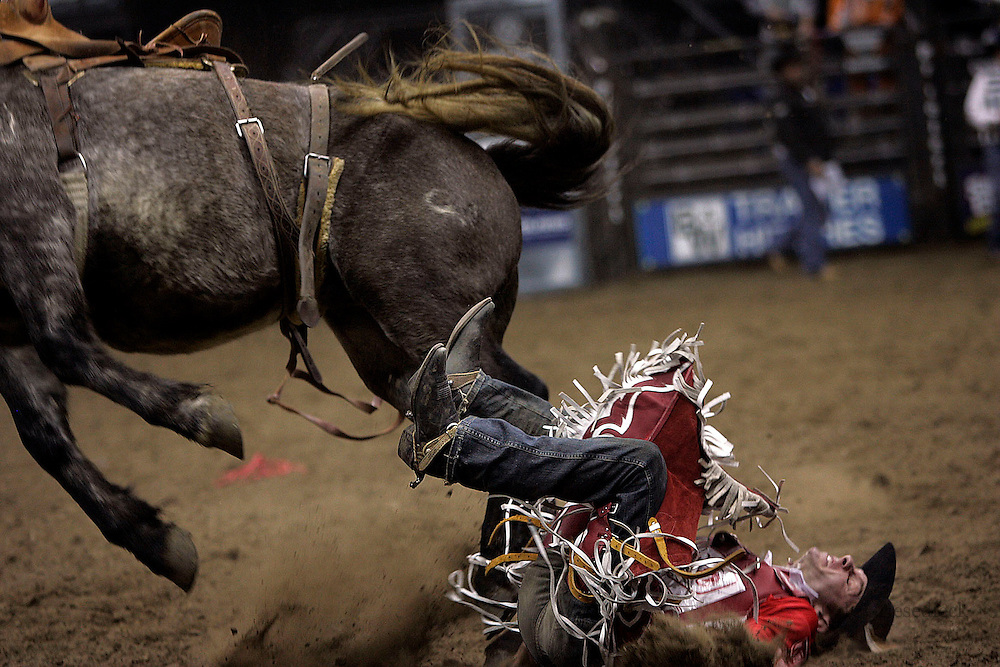 A rodeo cowboy lands flat on his back in pain after being bucked from a horse in the Toughest Cowboy competition.