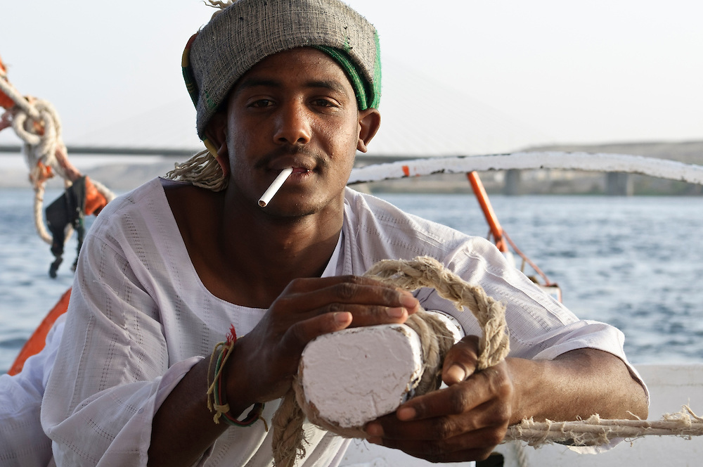An Egyptian felucca captain with his hands on the rudder and a cigarette in his mouth as he cruises down the Nile River near Aswan, Egypt