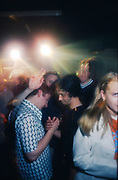 Young men clasping hands at a rave, UK, 1980s.