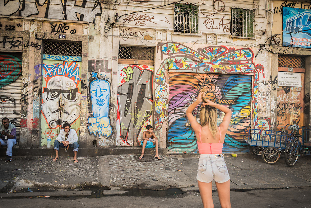 Girl in shorts in front of a wall with graffiti in the former red light district of Lapa, Rio de Janeiro, Brazil.