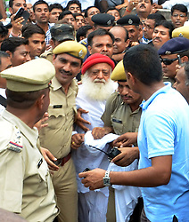 April 25, 2018 - FILE - An Indian spiritual guru who claims to have millions of followers worldwide has been found guilty of rape. A court in the northern city of Jodhpur ruled that ASARAM BAPU raped a 16-year-old girl in 2013 at his ashram there. He is likely to appeal against the verdict in a higher court. The guru, who is 77, has 400 ashrams around the world where he teaches meditation and yoga. PICTURED: Sep. 3, 2013 Jodhpur, India - Asaram Bapu is escorted away for court after sentencing. Authorities charged the 72-year old guru with raping a 16-year-old schoolgirl at one of his ashrams, or religious centers, in August. (Credit Image: © Xinhua via ZUMA Wire)