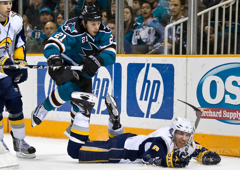 January 23, 2010; San Jose, CA, USA; San Jose Sharks defenseman Alexei Semenov (21) trips Buffalo Sabres center Derek Roy (9) during the second period at HP Pavilion. San Jose defeated Buffalo 5-2. Mandatory Credit: Jason O. Watson / US PRESSWIRE
