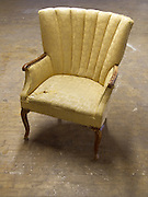 an old arm chair with a worn fabric seat