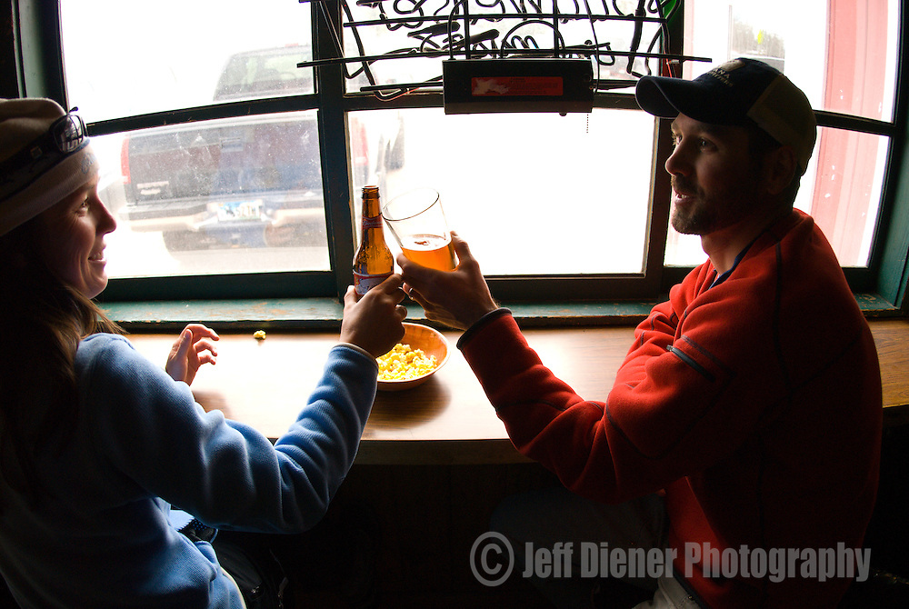A young couple celebrates apres ski at the StageCoach Bar in Wilson, Wyoming.