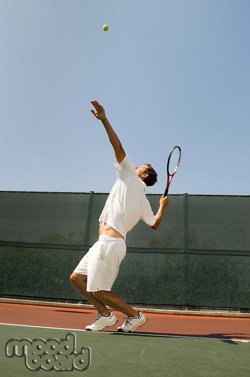 Man Serving Tennis Ball on tennis court