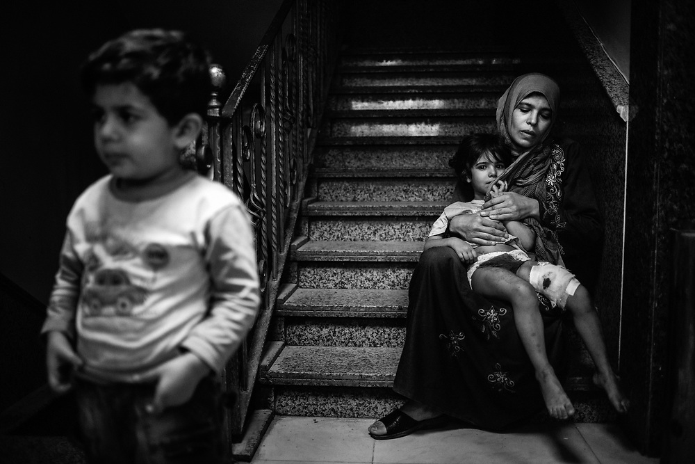 Syria, Aleppo, 2012/10/01.<br /> Inside the Dar Al-Shifaa hospital.<br /> The young girl, injured by mortar fragments,  rests in her mother's arms, while waiting for medical treatment.<br /> The young boy on the left is a daily witness of the civilian massacre, being the son of a doctor, who lives in the hospital with his family.