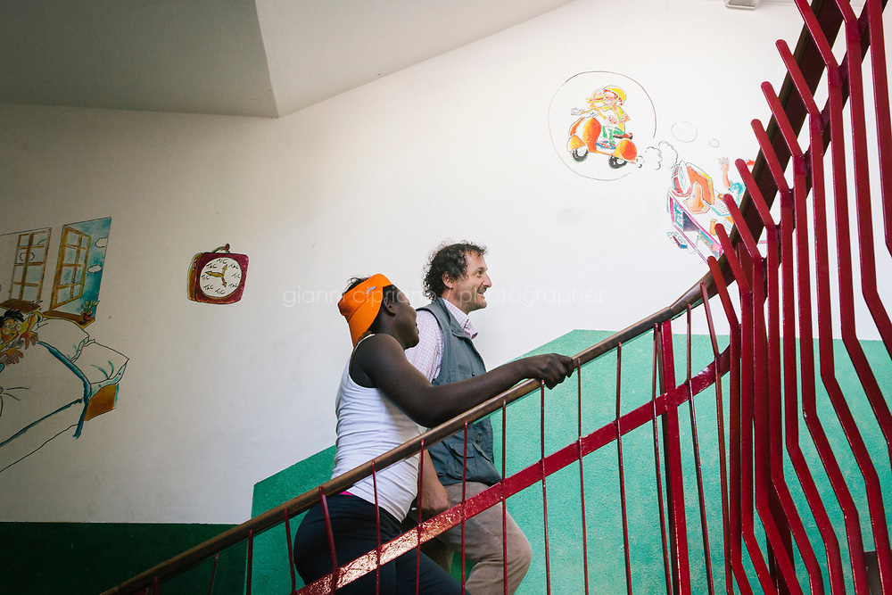 COMO, ITALY - 21 JUNE 2017: Giusto Della Valle, a local priest who since 2011 has run a center on the outskirts of town where more than 50 migrants sleep at night, walks up the stairs of the center with a migrant he hosts, in Como, Italy, on June 21st 2017.<br /> <br /> Residents of Como are worried that funds redirected to migrants deprived the town&rsquo;s handicapped of services and complained that any protest prompted accusations of racism.<br /> <br /> Throughout Italy, run-off mayoral elections on Sunday will be considered bellwethers for upcoming national elections and immigration has again emerged as a burning issue.<br /> <br /> Italy has registered more than 70,000 migrants this year, 27 percent more than it did by this time in 2016, when a record 181,000 migrants arrived. Waves of migrants continue to make the perilous, and often fatal, crossing to southern Italy from Africa, South Asia and the Middle East, seeing Italy as the gateway to Europe.<br /> <br /> While migrants spoke of their appreciation of Italy&rsquo;s humanitarian efforts to save them from the Mediterranean Sea, they also expressed exhaustion with the country&rsquo;s intricate web of permits and papers and European rules that required them to stay in the country that first documented them.