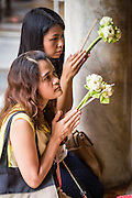 """21 JULY 2013 - BANGKOK, THAILAND: Women make merit and pray at Wat Benchamabophit on the first day of Vassa, the three-month annual retreat observed by Theravada monks and nuns. On the first day of Vassa (or Buddhist Lent) many Buddhists visit their temples to """"make merit."""" During Vassa, monks and nuns remain inside monasteries and temple grounds, devoting their time to intensive meditation and study. Laypeople support the monastic sangha by bringing food, candles and other offerings to temples. Laypeople also often observe Vassa by giving up something, such as smoking or eating meat. For this reason, westerners sometimes call Vassa the """"Buddhist Lent.""""         PHOTO BY JACK KURTZ"""