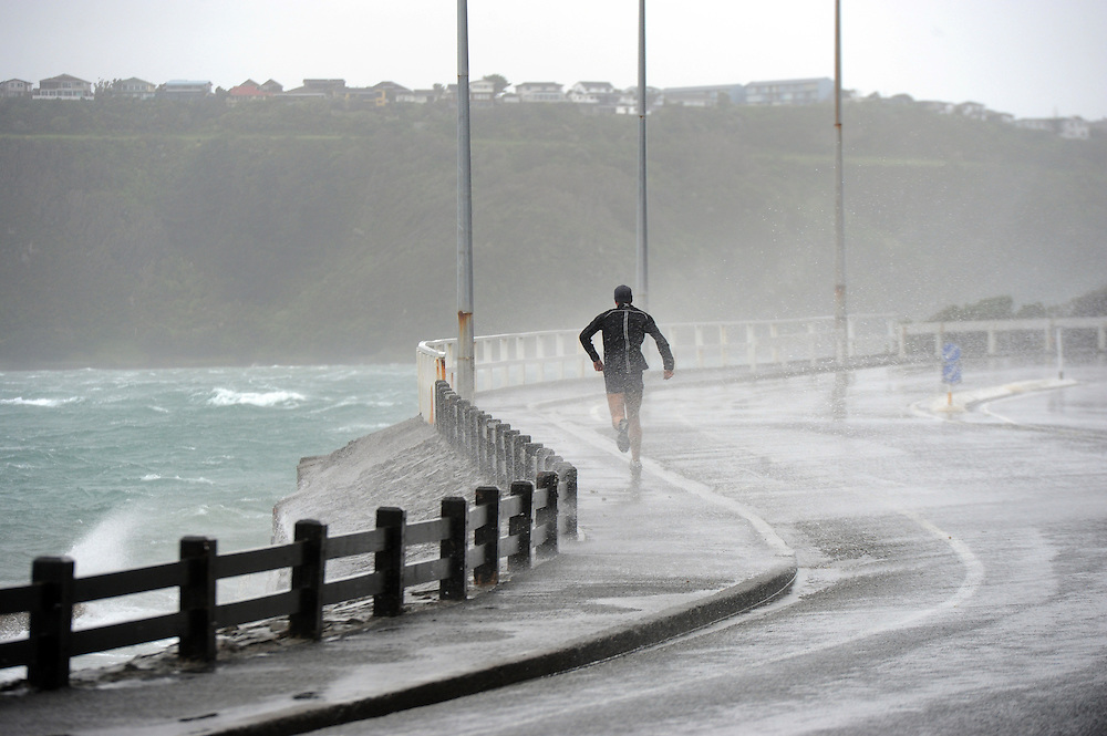 Waves break over the footpath on Balaena Bay as high winds lash the capital, Wellington, New Zealand, Monday, October 14, 2013. Credit:SNPA / Ross Setford