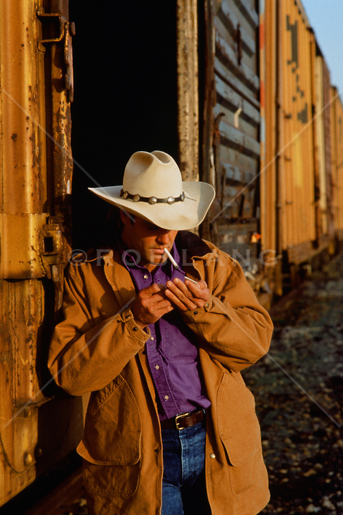cowboy lighting a cigarette and leaning against a train in New Mexico