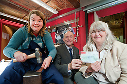 Second year Freeman College student Saskia Khan works on a hand forged copper spoon as  Ian Slater Chairman of Hospitality Sheffield hands over a cheque for £381 to Helen Kippax principal of Freeman College..Tuesday 11th October 2011. Image © Paul David Drabble