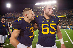 Oct 22, 2016; Morgantown, WV, USA; West Virginia Mountaineers quarterback Skyler Howard (3) and West Virginia Mountaineers offensive lineman Tyler Orlosky (65) celebrate after the game against the TCU Horned Frogs at Milan Puskar Stadium. Mandatory Credit: Ben Queen-USA TODAY Sports