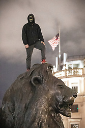 © Licensed to London News Pictures . 05/11/2019. London, UK. A man wearing a mask stands on a lion in Trafalgar Square . Supporters of Anonymous , many wearing Guy Fawkes masks , attend the Million Mask March bonfire night demonstration , in Trafalgar Square in central London . Photo credit: Joel Goodman/LNP