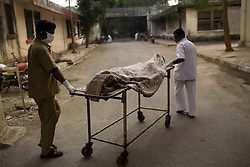 Orderlies at the Group of TB Hospitals transport the body of a recently deceased patient to the hospital morgue.