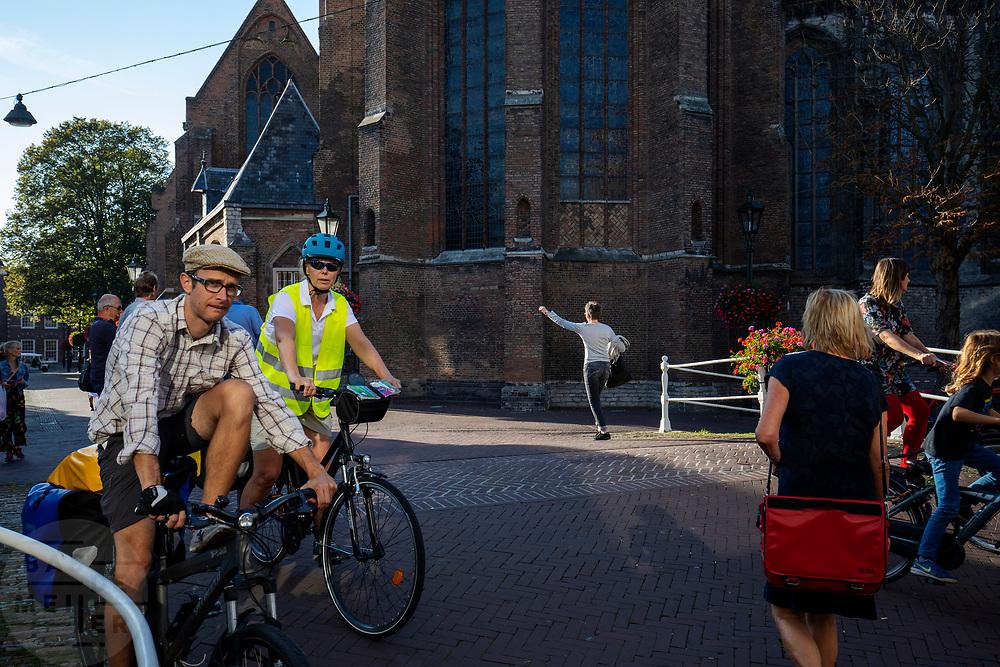 Toeristen op de fiets in de binnenstad van Delft.<br /> <br /> Tourists on the bike at the city center of Delft.