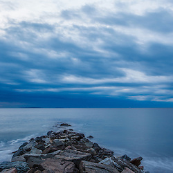 A cloudy dawn over the breakwater at Wallis Sands State Park in Rye, New Hampshire.