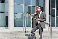 Smiling businessman using cell phone while standing on steps outside office