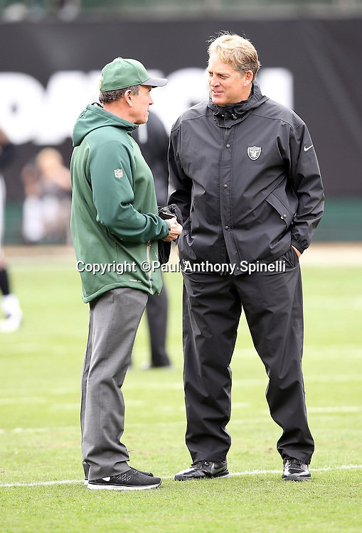 Oakland Raiders head coach Jack Del Rio talks to Green Bay Packers defensive coordinator Dom Capers before the 2015 week 15 regular season NFL football game against the Green Bay Packers on Sunday, Dec. 20, 2015 in Oakland, Calif. The Packers won the game 30-20. (©Paul Anthony Spinelli)