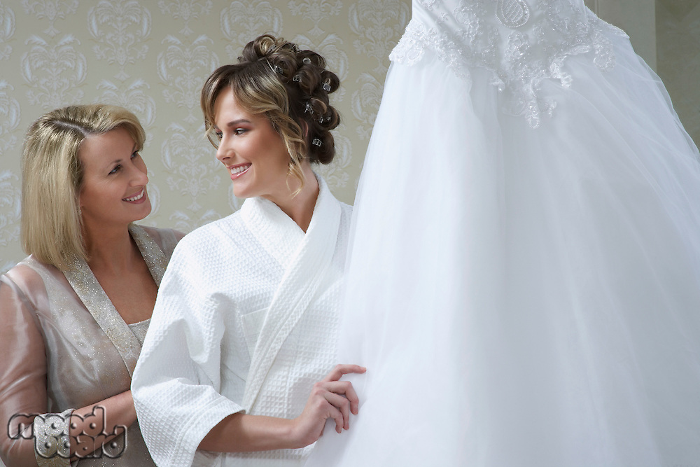 Bride in bathrobe touching wedding dress, mother looking on