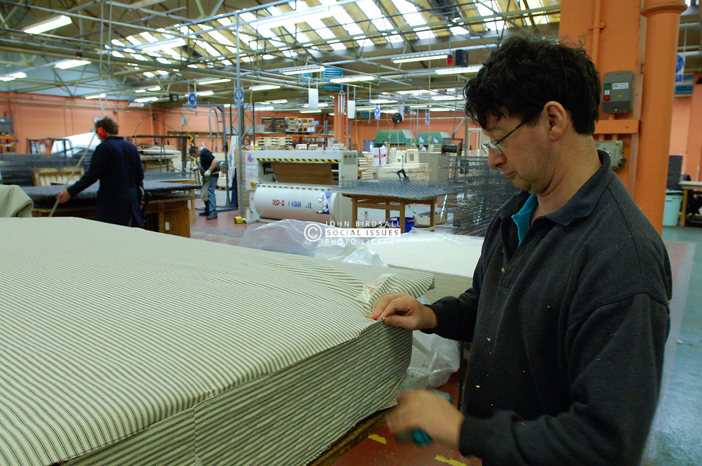 Remploy factory; Forest Hall; Newcastle; UK 2007, Remploy provides specialist employment services to disabled people and those who face barriers to employment, Man making mattress stitching down edging