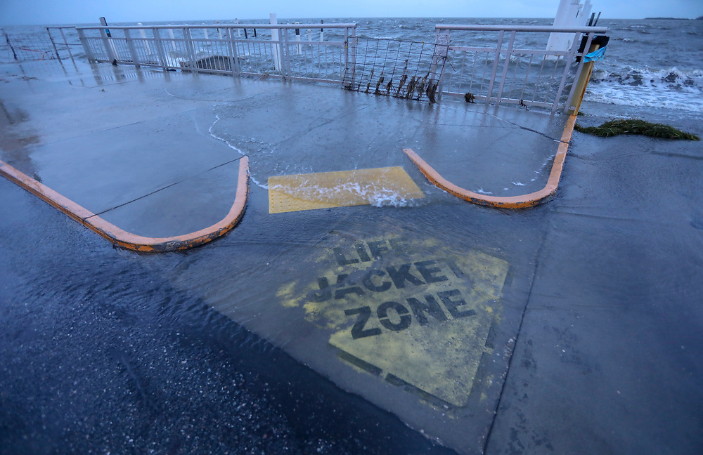 A painted sign on the ground near the boat launch along Dock Street is flooded with water Wednesday, Oct. 10, 2018 in Cedar Key. A combined high tide and storm surge from Hurricane Michael pushed water into the low lying streets of small town Wednesday. Hurricane Michael first made landfall near Mexico Beach in the panhandle area of Florida as a catastrophic Category 5 hurricane.