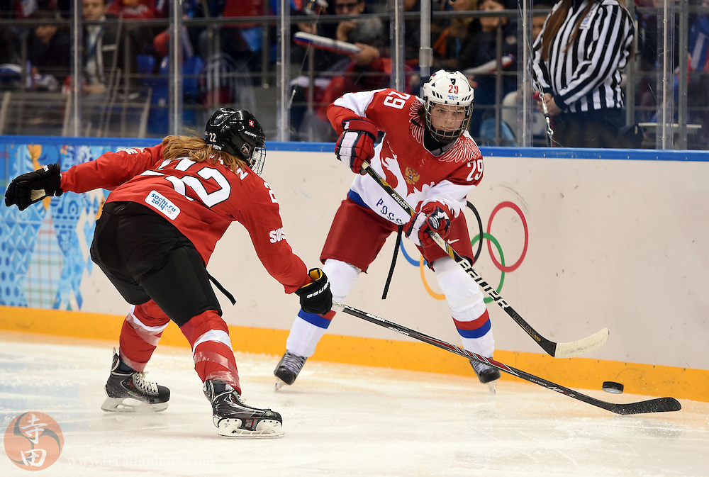 Feb 15, 2014; Sochi, RUSSIA; Russia forward Anna Shokhina (29) passes the puck as Switzerland defenseman Livia Altmann (22) defends in a women's quarterfinals ice hockey game during the Sochi 2014 Olympic Winter Games at Shayba Arena.