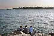Turkije, Istanbul, 4-6-2011Straatbeeld. Langs de Bosporus aan de aziatische kant. Drie jonge mannen zitten aan de waterkant.Foto: Flip Franssen