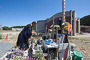 A Buddhist priest offers prayer for the 74 elementary school students and teachers who were swept away during the March 11 tsunami, at a makeshift  shrine outside Okawa elementary school in Ishinomaki, Miyagi Prefecture, Japan on 07 Sept. 2011. The fate of the school, where 84 pupils and teachers perished in the tsunami, is still undecided as residents and leading community figures are debating the value of leaving the structure standing. Photograph: Robert Gilhooly