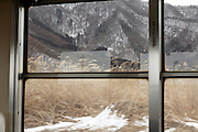 looking out of the window towards mountains on a train trip in Nagano prefecture Japan