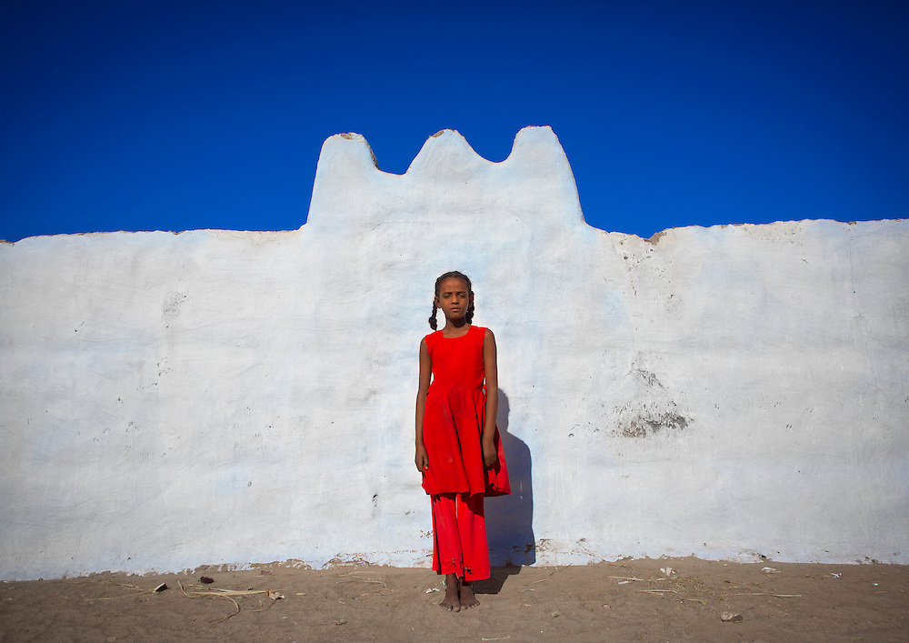 Girl standing in front of a wall in Tumbus, Sudan. The Nubian houses are short and split into two: one side for men and guests, the other side for women.