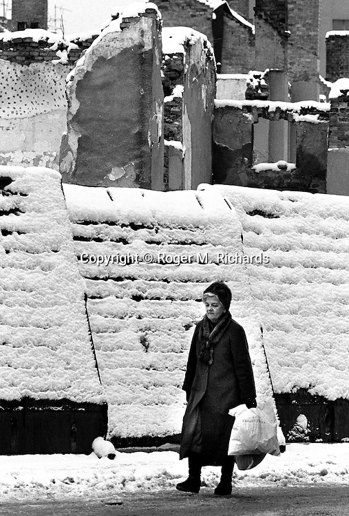 A woman walks past snow-covered buildings in downtown during the final days of the siege of the city, Sarajevo, Bosnia and Herzegovina, January 1996. PHOTO BY ROGER RICHARDS
