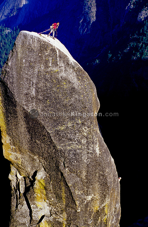 YOSEMITE, CA - A rock climber looks down the Lost Arrow Spire for his climbing partner ascending the cliff, Yosemite, California.  The Lost Arrow Spire sits next to Yosemite Falls and was first climbed in 1947 by John Salathe.  (releasecode: jk_mr1008) (Model Released)