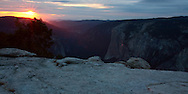 As the sun sets on Sentinel Dome, the last rays shine red on the face of El Capitain. Yosemite National Park, CA