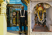 Ceremonial guard and garlanded religious statue, Kathmandu, Nepal