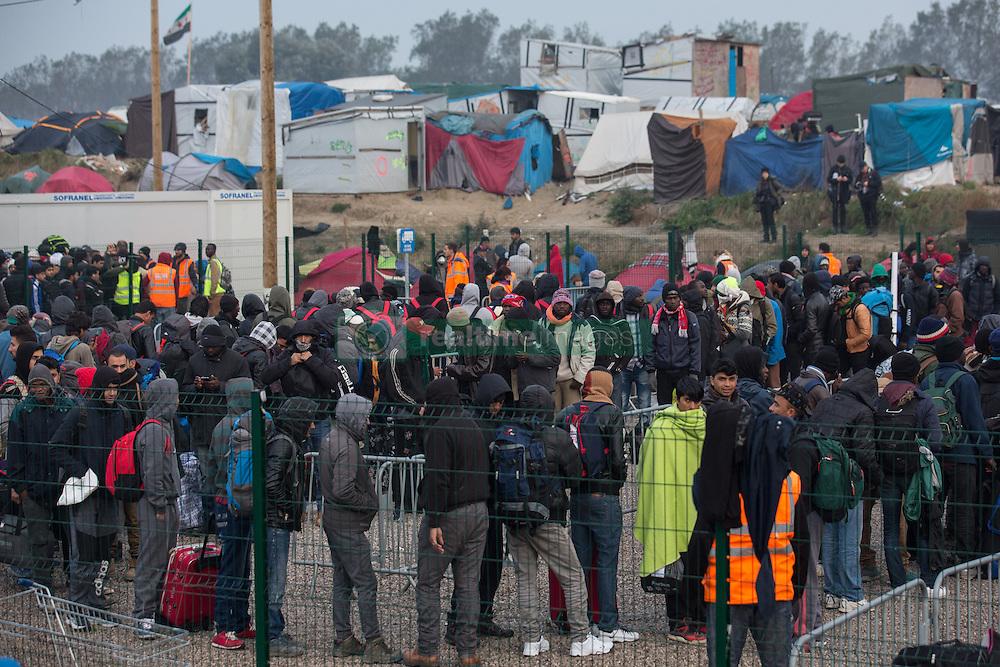 Dschungel von Calais: Das wilde Fl&cedil;chtlingslager wird ger&permil;umt und die Fl&cedil;chtlinge in Aufnahmezentren verteilt / 241016 ***Calais, Pas-de-Calais, France - 24.10.2016    <br />  <br /> Refugees line up to leave the camp. Start of the eviction on the so called &icirc;Jungle&quot; refugee camp on the outskirts of the French city of Calais. Refugees and migrants leaving the camp to get with buses to asylum facilities in the entire country. Many thousands of migrants and refugees are waiting in some cases for years in the port city in the hope of being able to cross the English Channel to Britain. French authorities announced a week ago that they will evict the camp where currently up to up to 10,000 people live.<br /> <br /> <br /> Fluechtlinge stehen in einer Reihe um das Camp zu verlassen. Beginn der Raeumung des so genannte &icirc;Jungle&icirc;-Fluechtlingscamp in der franz&circ;sischen Hafenstadt Calais. Fluechtlinge und Migranten verlassen das Camp um mit Bussen zu unterschiedlichen Asyleinrichtungen gebracht zu werden. Viele tausend Migranten und Fluechtlinge harren teilweise seit Jahren in der Hafenstadt aus in der Hoffnung den Aermelkanal nach Groflbritannien ueberqueren zu koennen. Die franzoesischen Behoerden kuendigten vor einigen Wochen an, dass sie das Camp, indem derzeit bis zu bis zu 10.000 Menschen leben raeumen werden. <br /> <br /> Photo: Bjoern Kietzmann