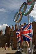 London lady stands for a souvenir photo on the Olympic rings that stand at the entrance of King Henry the Eighth's Hampton Court Palace on the first day of competition of the London 2012 Olympic 250km mens' road race. Starting from central London and passing the capital's famous landmarks before heading out into rural England to the gruelling Box Hill in the county of Surrey. Local southwest Londoners lined the route hoping for British favourite Mark Cavendish to win Team GB first medal but were eventually disappointed when Kazakhstan's Alexandre Vinokourov eventually won gold.
