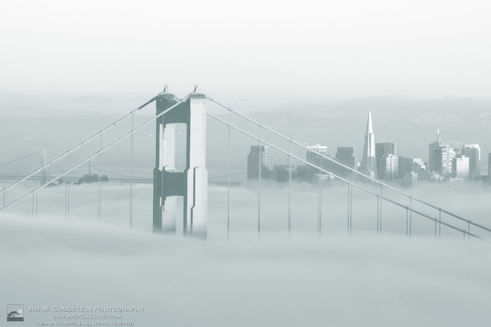 Fog rolls through the San Francisco bay covering the Golden Gate Bridge and city. Pictured is the top of the Golden Gate Bridge's north span sticking out of the fog with the San Francisco skyline in the background.