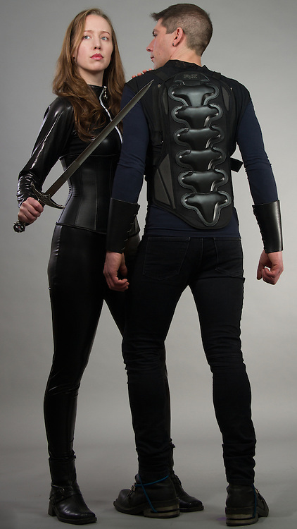 Couple posing together with the woman in a catsuit and the man in motorcycle gear.