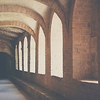 sunlight shining between the arches of a history french abbey