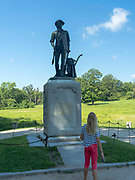 A girl reads the inscription on the Minute Man Statute, Minute Man National Historic Site, Concord, Massachusetts, USA.