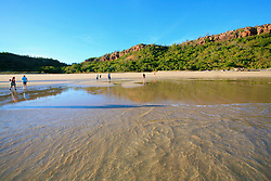 Tourists walking on an isolated Kimberley beach at Bat Island
