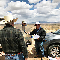 John Boomer, foreground, a member of the Multicultural Alliance for a Safe Environment, listens as Dick Johnson, a contractor for the U.S. Department of Energy, talks about contamination at the former Bluewater uranium mill while Mark Kautsky, site manager for DOE's Office of Legacy Management, holds a map of the site.