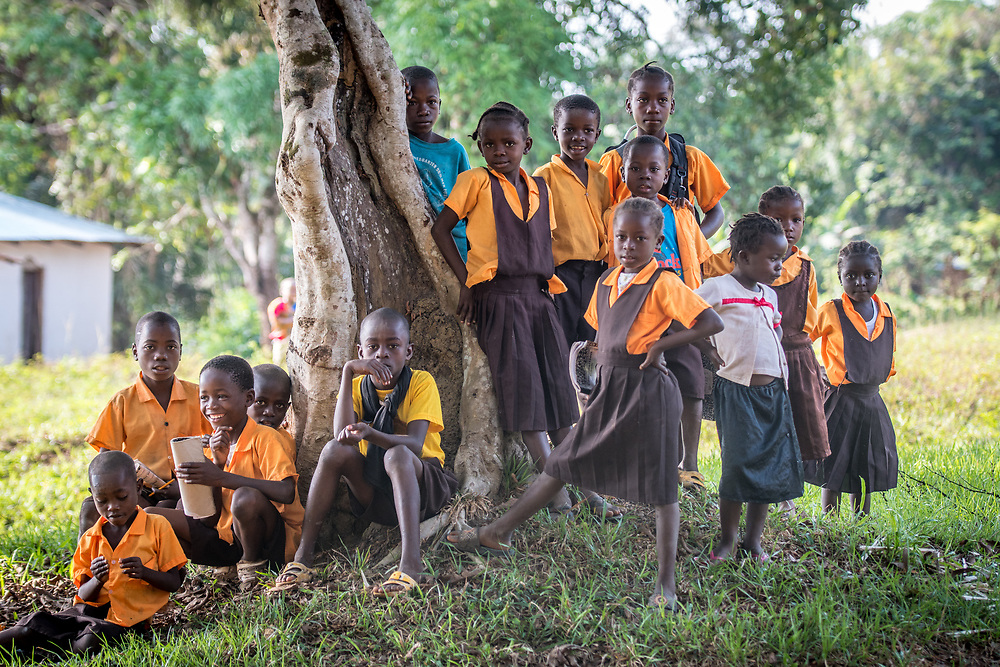 A group of school children in uniforms gathers under a tree in Ganta, Liberia