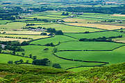 Pastoral view of hedgerows and farms from Muncaster Fell. England Coast to Coast hike with Wilderness Travel, day 1 of 14: Starting with dipping our boots in the Irish Sea at Ravenglass in Lake District National Park, we ascended Muncaster Fell, seeing the ruins of a Roman bathhouse along the way. We then passed Muncaster Castle  and descended into Miterdale. Overnight in Irton Hall, Eskdale, Holmrook, Cumbria county, England, United Kingdom, Europe. Irton Hall is a large, mostly 1800s house with a 1300s tower.  [This image, commissioned by Wilderness Travel, is not available to any other agency providing group travel in the UK, but may otherwise be licensable from Tom Dempsey – please inquire at PhotoSeek.com.]