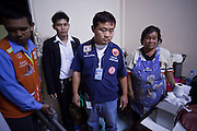 """Oct. 1, 2009 -- BANGKOK, THAILAND: Volunteers from Poh Teck Tung and neighbors crowd into the apartment of a woman who attempted suicide in Bangkok. The 1,000 plus volunteers of the Poh Teck Tung Foundation are really Bangkok's first responders. Famous because they pick up the dead bodies after murders, traffic accidents, suicides and other unplanned, often violent deaths, they really do much more. Their medics respond to medical emergencies, from minor bumps and scrapes to major trauma. Their technicians respond to building collapses and traffic accidents with heavy equipment and the """"Jaws of Life"""" and their divers respond to accidents in the rivers and khlongs of Bangkok. The organization was founded by Chinese immigrants in Bangkok in 1909. Their efforts include a hospital, college tuition for the poor and tsunami relief.    Photo by Jack Kurtz / ZUMA Press"""