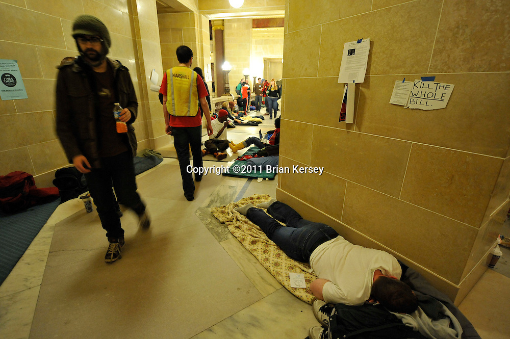 A protester sleeps in the state capitol in Madison, Wisconsin on February 23, 2011. Thousands are staging a 24-hour protest of the state budget proposed by Republican Gov. Scott Walker, which includes cuts in benefits for state workers and takes away many of their collective bargaining rights.  (Photo by Brian Kersey)