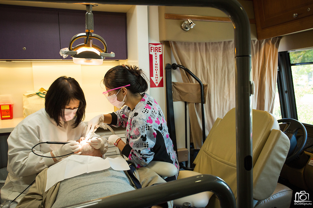 Registered Dental Hygienist Suishan Huang (left) and Dental Assistant Yuyao Xu perform basic cleaning on Donald Richter's teeth during the Agape Dental Mobile Clinic at the Barbara Lee Senior Center in Milpitas, California, on July 26, 2013. (Stan Olszewski/SOSKIphoto)
