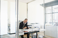 Businessman sitting at desk in office talking on phone.